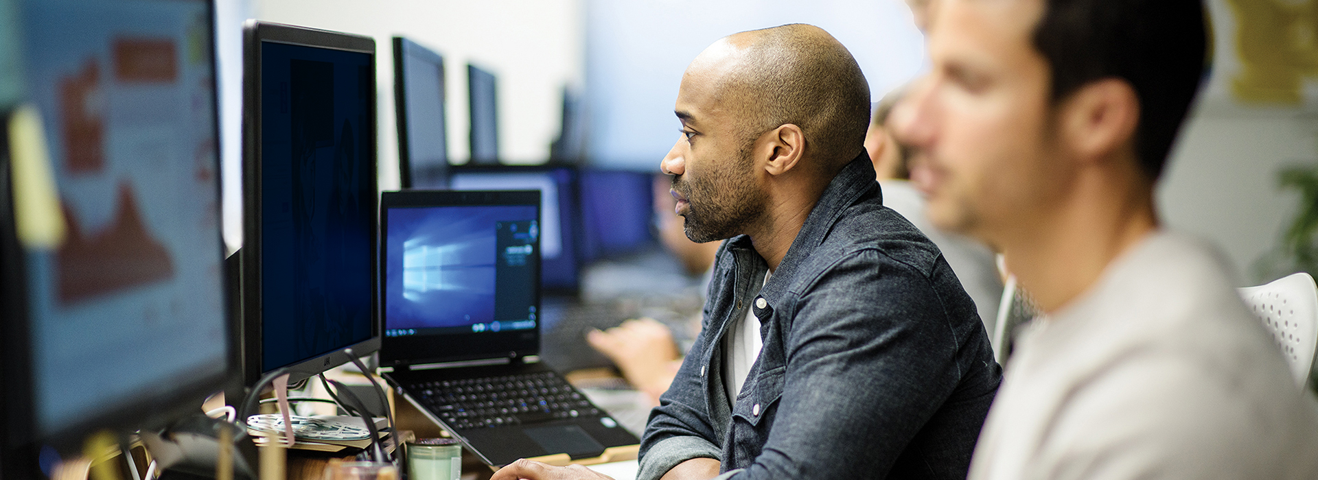 Photo of two Microsoft employees look at a computer monitor