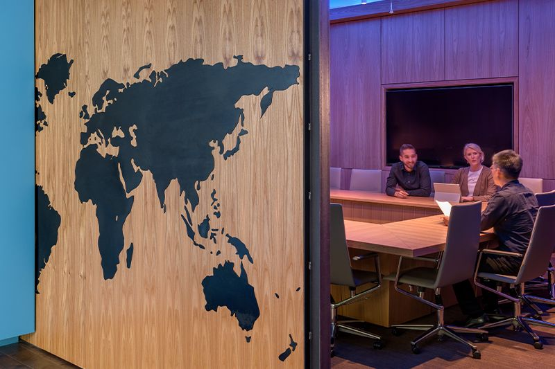 Photo of three employees talking in conference room