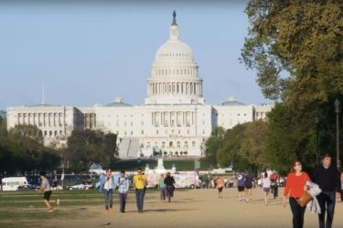 Photo of people walking in front of US Capital building