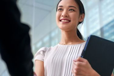 An image of a woman holding a folder smiling