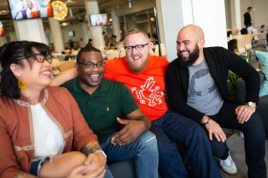 Image of four people sitting on a couch laughing