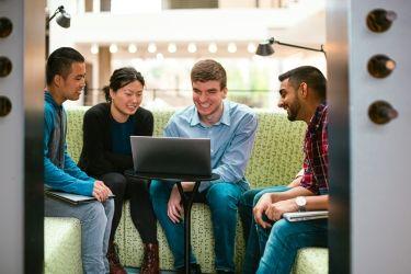 Photo of Microsoft employees around laptop having a conversation