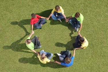Children sitting in circle holding hands