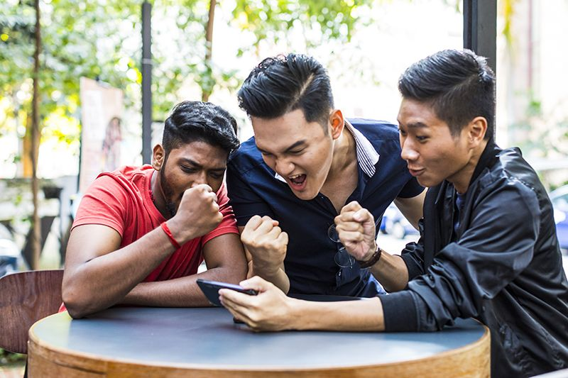 Photo of college students watching video on mobile phone.