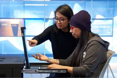 Photo of two developers looking at laptop screen