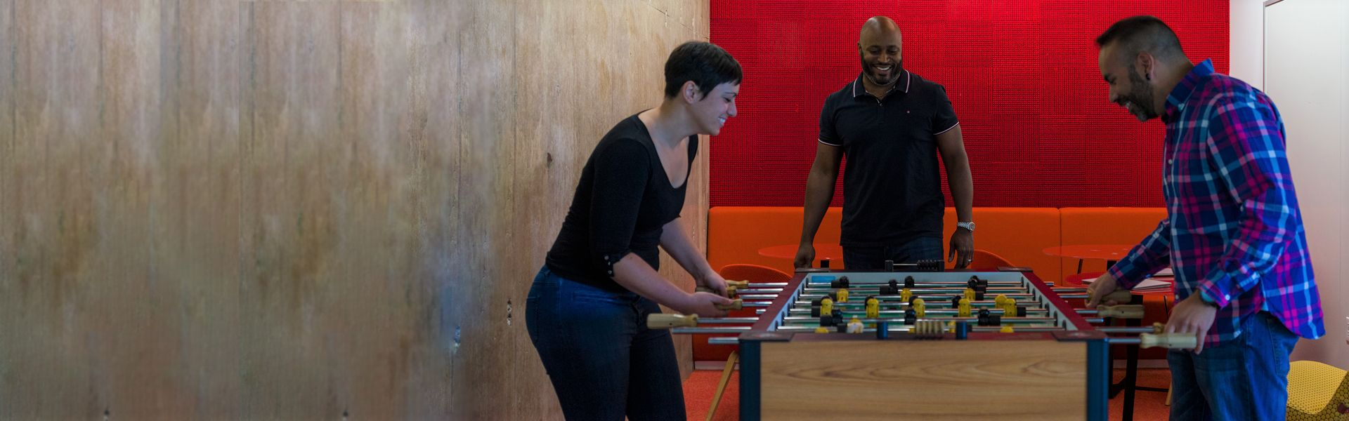 Photo of 3 students playing Foosball